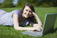 Woman Using Laptop On Grass Stock Image