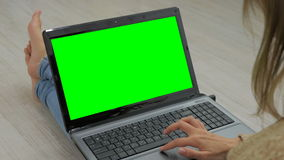 Woman using laptop with green screen. Woman`s hands typing on a laptop keyboard. Business, communication, freelance and internet concept stock video