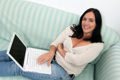 Woman using a laptop. Happy Black haired woman using a laptop on couch Royalty Free Stock Image