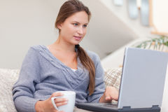 Woman using a laptop while having a coffee Royalty Free Stock Photography