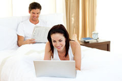 Woman using laptop on her bed Stock Image
