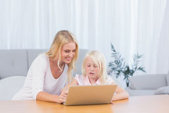 Woman using laptop with her daughter Royalty Free Stock Image