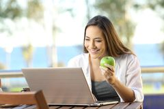 Woman using a laptop and holding an apple outdoors. Happy woman using a laptop and holding an apple outdoors in a hotel or house balcony Stock Image
