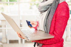 Woman using laptop and holding credit card Royalty Free Stock Photography