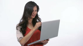 Woman using a laptop while holding it Stock Photos