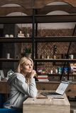 Pensive middle aged woman holding credit card and looking away while using laptop with facebook website. On screen royalty free stock photo
