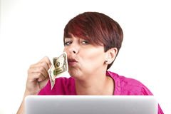 Woman using laptop and kissing a money Royalty Free Stock Image