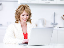 Woman using laptop in the kitchen Royalty Free Stock Photography