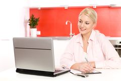 Woman using laptop in kitchen Royalty Free Stock Image