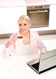 Woman using laptop in kitchen. Woman with coffee and laptop in kitchen Stock Photos