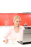 Woman using laptop in kitchen Stock Image