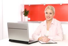 Woman using laptop in kitchen Royalty Free Stock Images