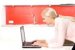 Woman using laptop in kitchen Stock Photography