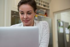 Woman using laptop in kitchen. At home Royalty Free Stock Photography