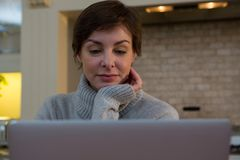 Woman using laptop in kitchen. At home Royalty Free Stock Photos