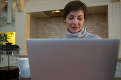 Woman using laptop in kitchen. At home Royalty Free Stock Image