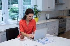 Woman using laptop in kitchen. At home Stock Images