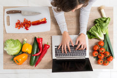 Woman Using Laptop In Kitchen. Young Woman Leaning On Countertop While Using Laptop In Kitchen Stock Photos