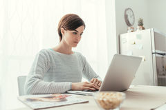 Woman using a laptop in the kitchen. Young woman sitting at kitchen table and working with a laptop, home and lifestyle concept Stock Image