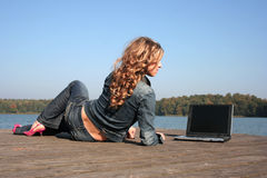 Woman using laptop by lake Royalty Free Stock Image