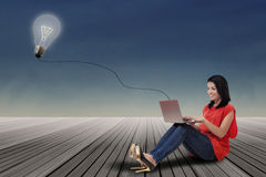 Woman using laptop with lightbulb outdoors Royalty Free Stock Photography