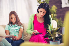 Woman using laptop  in living room while her daughter using phone Royalty Free Stock Photos