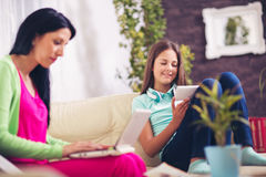Woman using laptop  in living room while her daughter using phone Royalty Free Stock Images