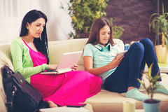 Woman using laptop  in living room while her daughter using phone Stock Photography