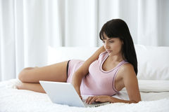 Woman Using Laptop While Lying In Bed Stock Photos