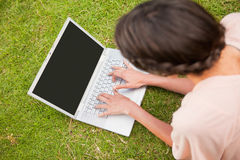 Woman using a laptop while lying in grass Stock Images
