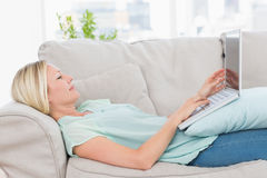 Woman using laptop while lying on sofa Royalty Free Stock Photos