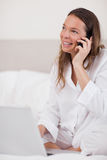 A woman using a laptop while making a phone call Stock Photography