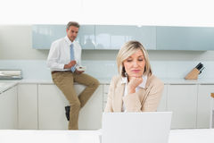 Woman using laptop and man in background at kitchen Royalty Free Stock Photography