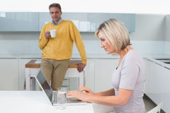 Woman using laptop and man with coffee cup at kitchen Stock Images