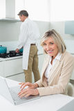 Woman using laptop and man cooking food in kitchen Stock Photos