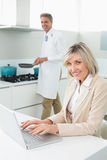 Woman using laptop and man cooking food Royalty Free Stock Photography