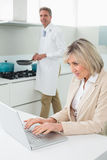 Woman using laptop and man cooking food Royalty Free Stock Images