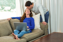 Woman using laptop and man kissing on her forehead Royalty Free Stock Photography