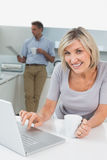 Woman using laptop and man reading newspaper in kitchen Royalty Free Stock Image