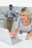 Woman using laptop and man reading newspaper in kitchen Stock Image