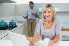 Woman using laptop and man reading newspaper in kitchen Royalty Free Stock Images