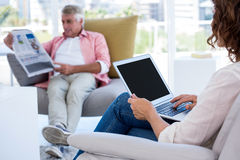 Woman using laptop while man reading newspaper Stock Photo