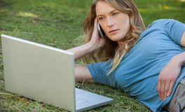 Woman using laptop and mobile phone at park Royalty Free Stock Photos