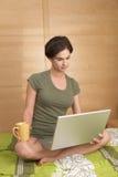 Woman using laptop in morning Stock Image