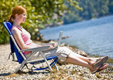 Woman using laptop near water Royalty Free Stock Images