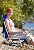 Woman using laptop near water stock photo