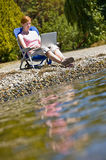 Woman using laptop near water Royalty Free Stock Photo