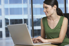 Woman Using Laptop At Office Desk Royalty Free Stock Image