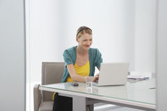 Woman Using Laptop In Office Royalty Free Stock Photo