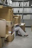 Woman Using Laptop In Office Storage Room stock photography